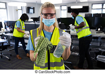 Portrait of Caucasian woman wearing hi vis vest, gloves, safety glasses and face mask, sanitizing office with colleagues in the background. Hygiene in workplace during Coronavirus Covid 19 pandemic.