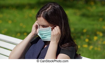 Portrait of woman wearing protective medical face mask for ...