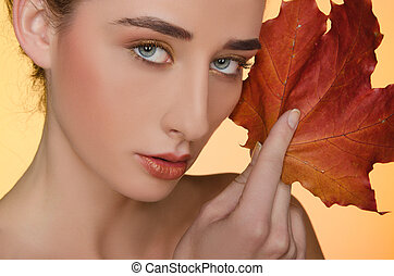 portrait of woman with autumn leaves on yellow background