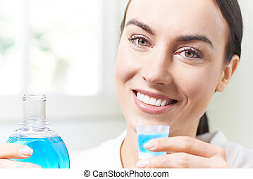 Portrait Of Woman With Beautiful Teeth Using Mouthwash In Bathroom