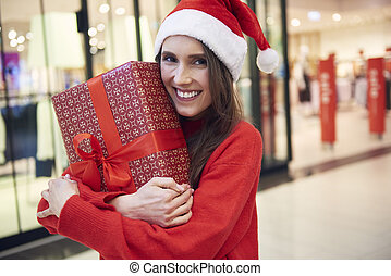 Portrait of woman with Christmas present at the store