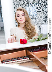 Portrait of woman with claret rose playing piano