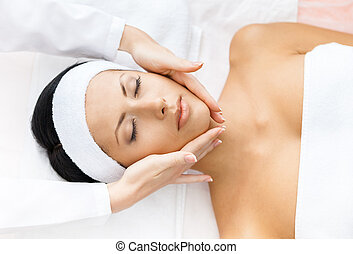Portrait of woman with closed eyes getting face massage
