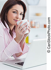 Portrait of woman with coffee cup and laptop