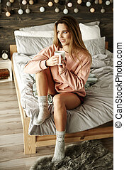 Portrait of woman with coffee sitting on bed
