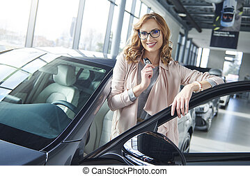 Portrait of woman with her brand new car