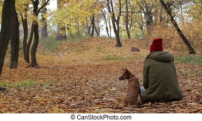 Portrait of woman with her dog in autumn park