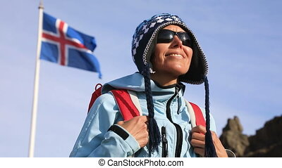 Portrait of woman with Iceland flag waving in wind -...