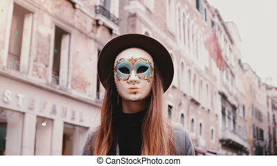 Portrait of woman with long hair and hat wearing a carnival mask standing in Venice street in Italy looking at camera.