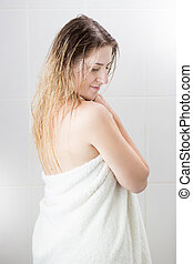 Portrait of woman with long hair wiping after having shower