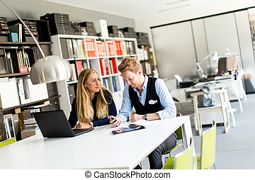Portrait of woman with male colleague working in office
