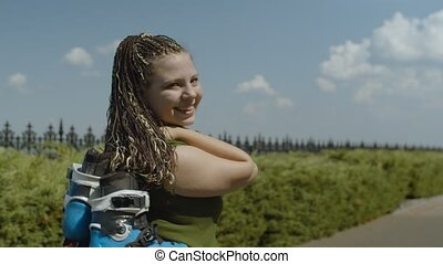 Portrait of joyful female turning around and smiling while walking along country park alley carrying inline roller skates on shoulder, happiness, enjoyment, satisfaction with good outdoors workout.