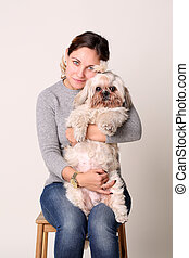 Portrait of woman with shih-tzu dog, sitting on chair in studio