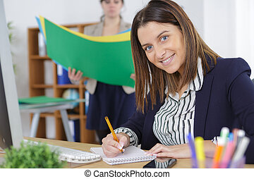 Portrait of woman writing in notepad