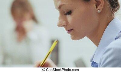 portrait of woman writing memo