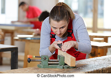 portrait of woodworking female student with chisel