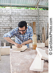 worker at carpenter workspace applying wood vinyl into a board u