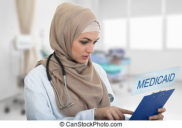 portrait of worried muslim female Medical doctor holding paperclip in hospital