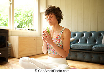 yoga woman sitting on floor at home drinking water