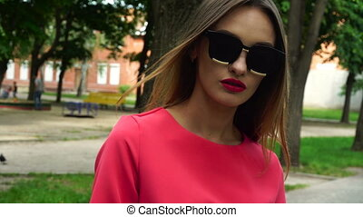 adorable blonde in sunglasses and red suit outdoors