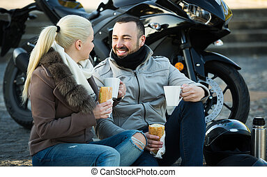 Portrait of young adults drinking coffee and chatting near motorcycle