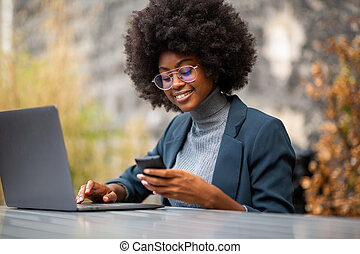young african american business woman smiling with with laptop and mobile phone