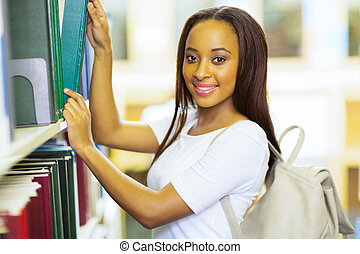 young african american college girl looking for book in library