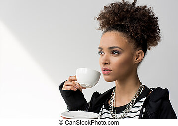 portrait of young african american girl holding cup of tea and looking away