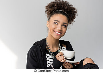 portrait of young african american girl holding cup of tea isolated on grey