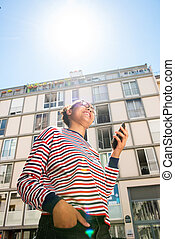 young african american girl standing outside with mobile phone