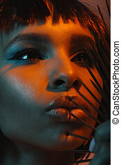 portrait of young african american girl touching lips with dangerous needles