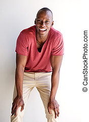 young african american man laughing with hands on knees