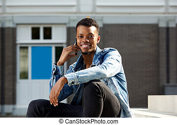 young african american man smiling outside with cellphone