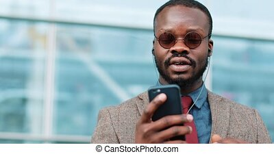 Portrait of young african american man talking using smartphone video chat technology stands next to the office center dressed in a business suit with sunglasses