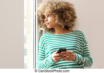 young african american woman holding mobile phone and looking out window
