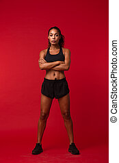 Portrait of young african american woman in black sportswear standing, isolated over red background