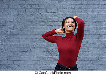 young african american woman laughing with hand in hair