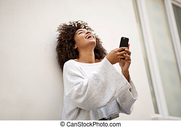 young african american woman laughing with mobile phone