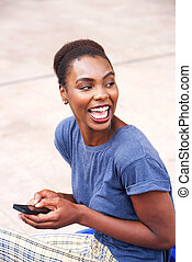 young african american woman laughing with mobile phone outdoors