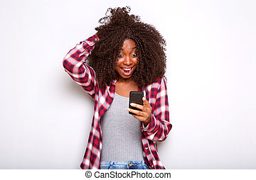 young african american woman looking at mobile phone with surprised expression on white background