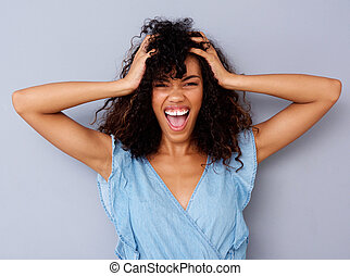 young african american woman shouting with hand in hair