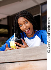 young african american woman sitting at cafe looking at mobile phone with surprised expression