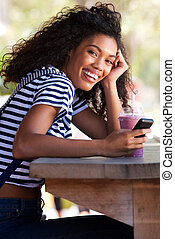 young african american woman sitting at cafe with cellphone