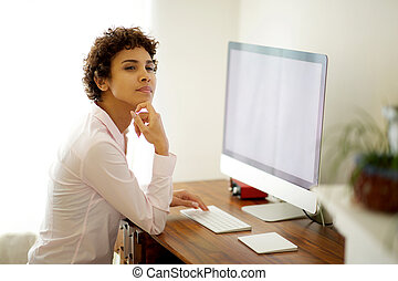 young african american woman sitting at desk with computer