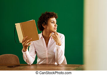 young african american woman sitting at home thinking with book