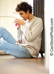 young african american woman sitting on floor against radiator heater drinking cup of tea