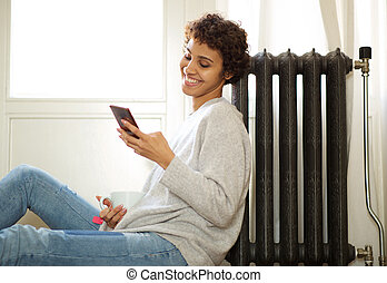 young african american woman sitting on floor next to radiator and looking at mobile phone