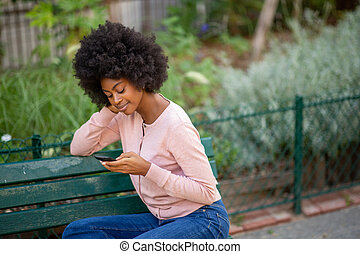 young african American woman sitting on park bench with cellphone in hand