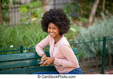 young african american woman sitting on park bench with phone in hand