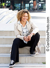 young african american woman sitting on stairs in city